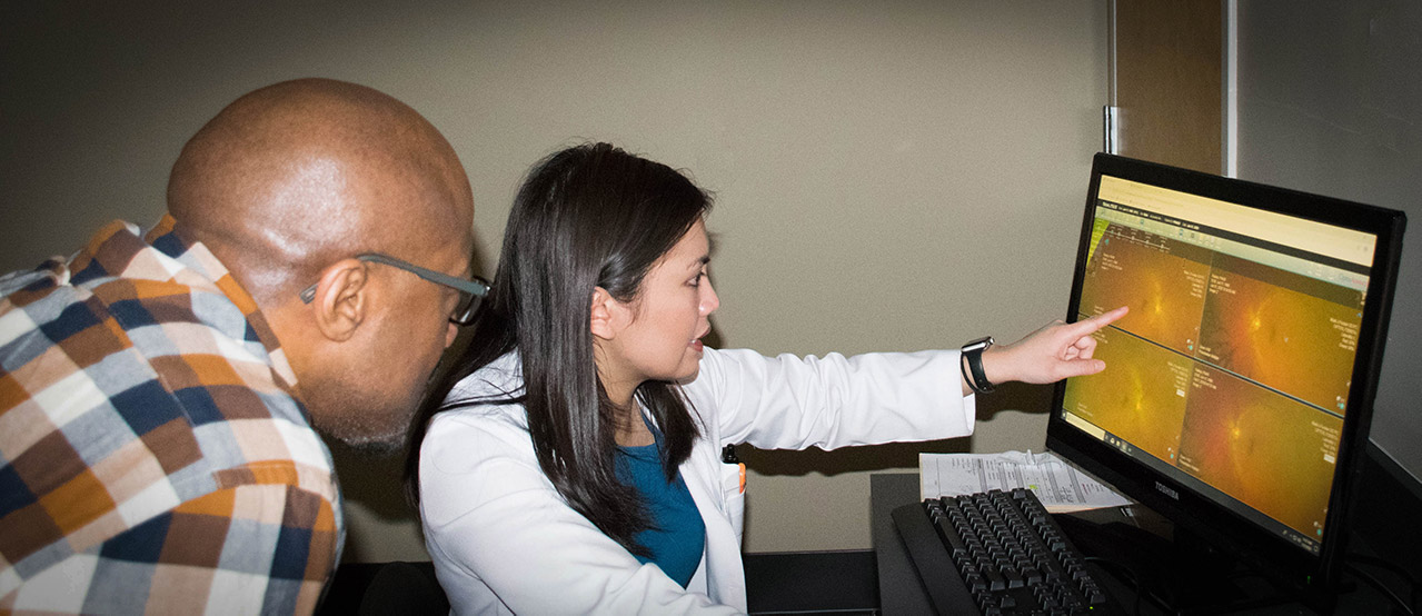 Dr. showing optomap image to patient