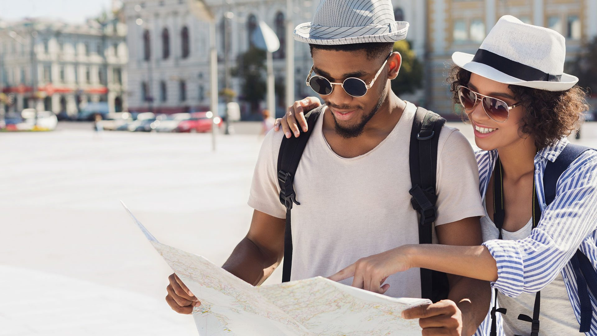 Couple with nice sunglasses looking at a map in a city