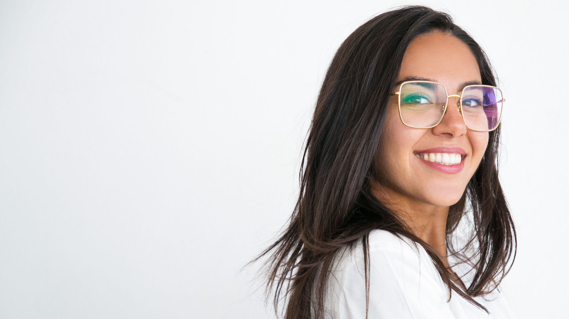 young woman in white shirt wearing gold glasses smiling